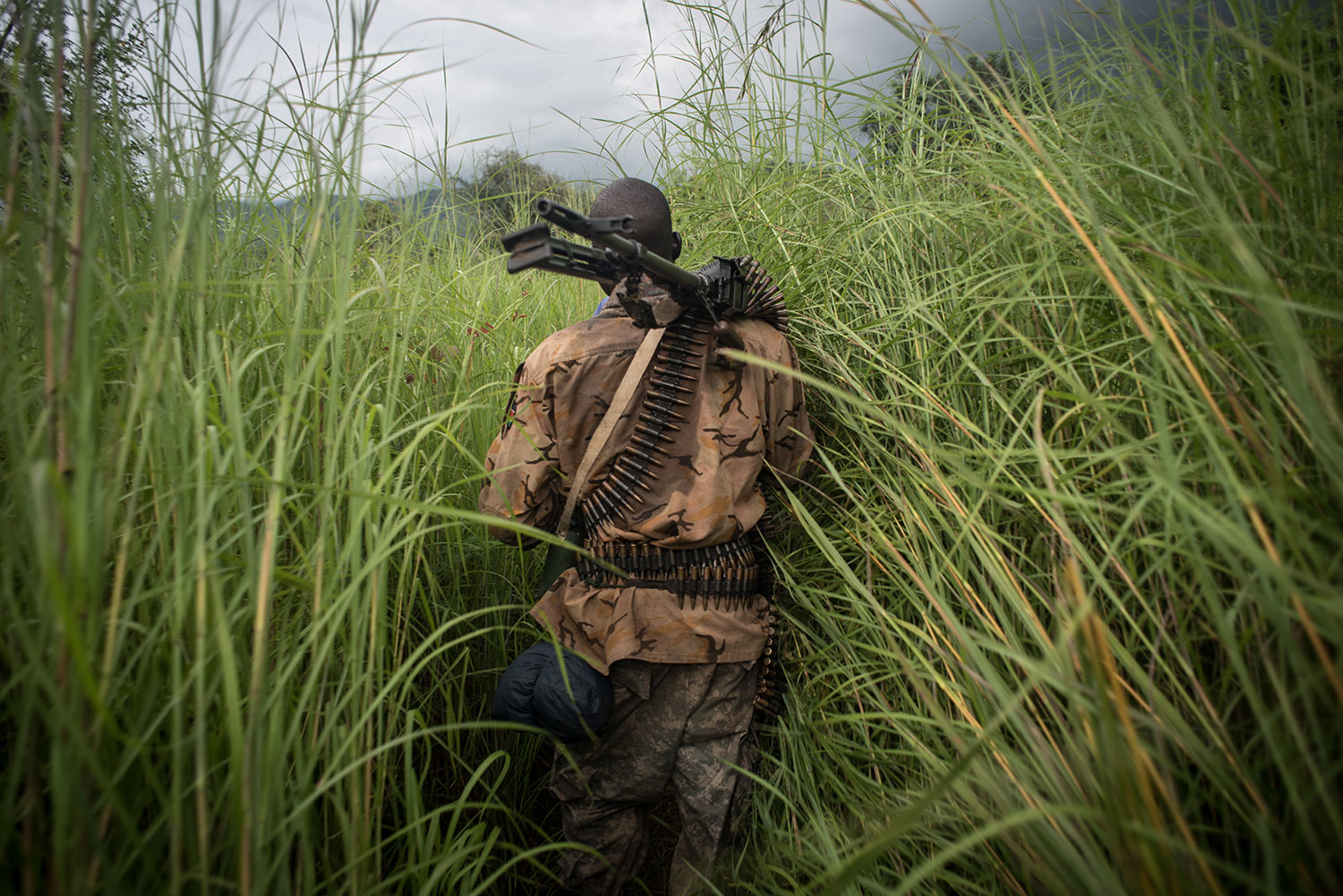 A SPLA-In Opposition soldier walks through the elephant grass in rebel-held Magwi county of South Sudan's Eastern Equatoria state on August 28, 2017. USHMM/Jason Patinkin.