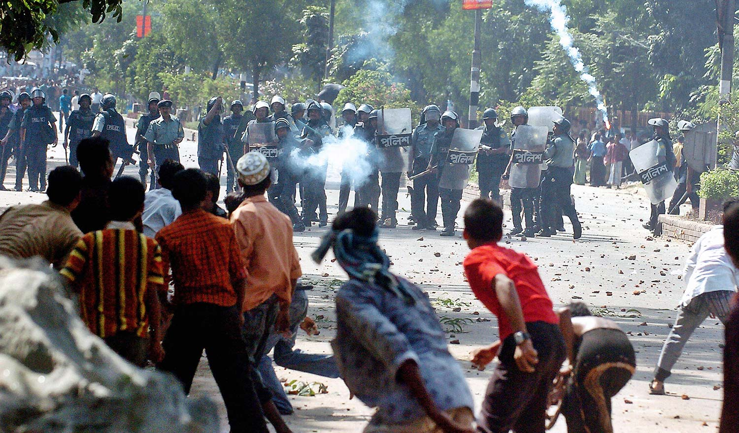 Bangladeshi policemen fire tear gas. Getty Images/Farjana K. Godhuly.